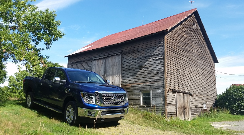 The 2016 Nissan Titan XD Cummins V-8 Turbo Diesel SL 4WD CC in Deep Blue Pearl outside a New York State Barn