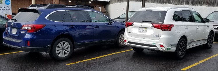 White Mitsubishi Outlander and Blue Subaru Outback