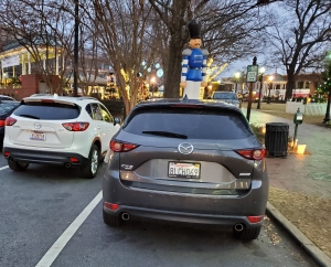 Two generations of Mazda CX5 parked by a tall Christmas Nutcracker in Marietta GA