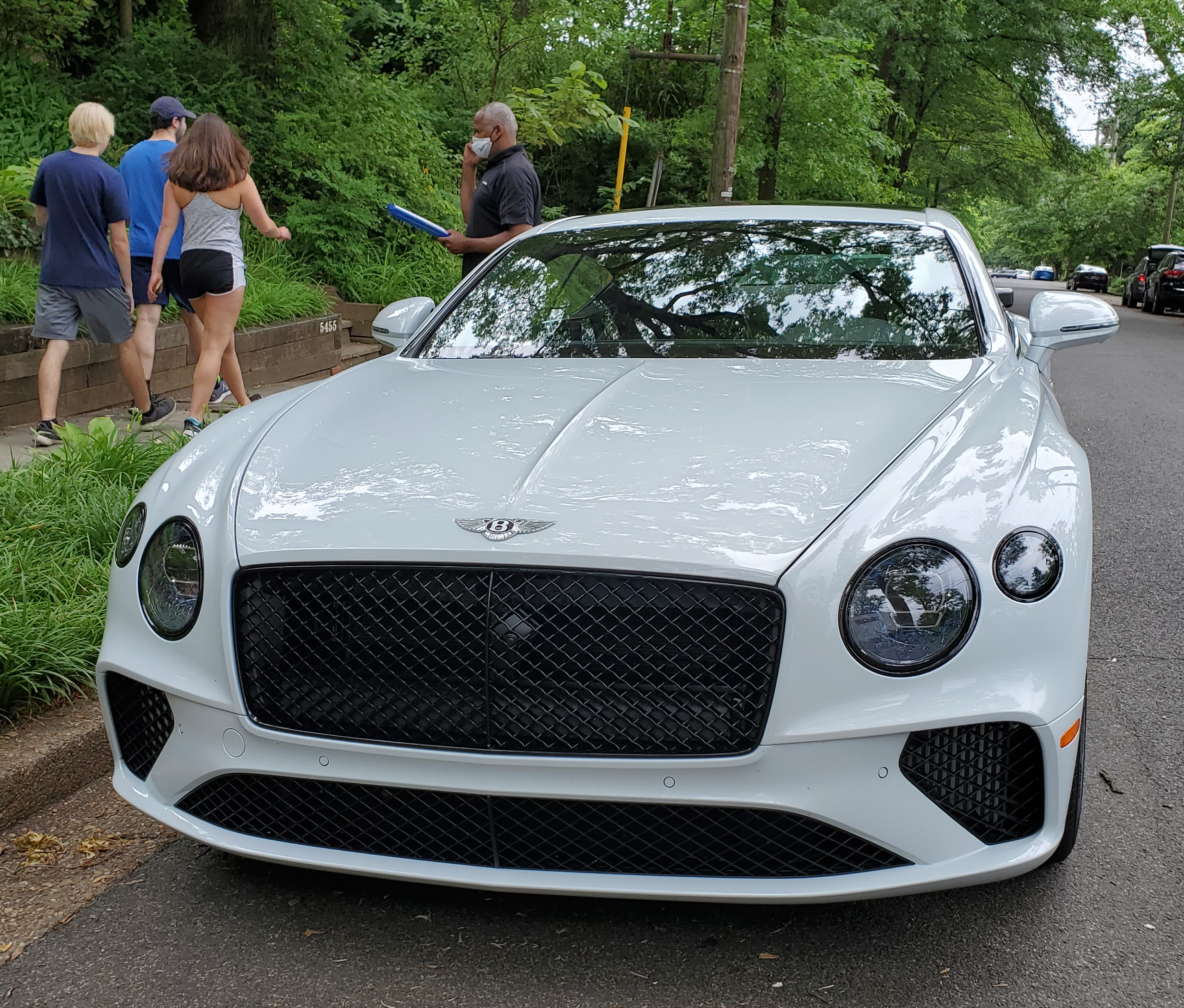 White Bentley Continental GT V8 with people beside it.