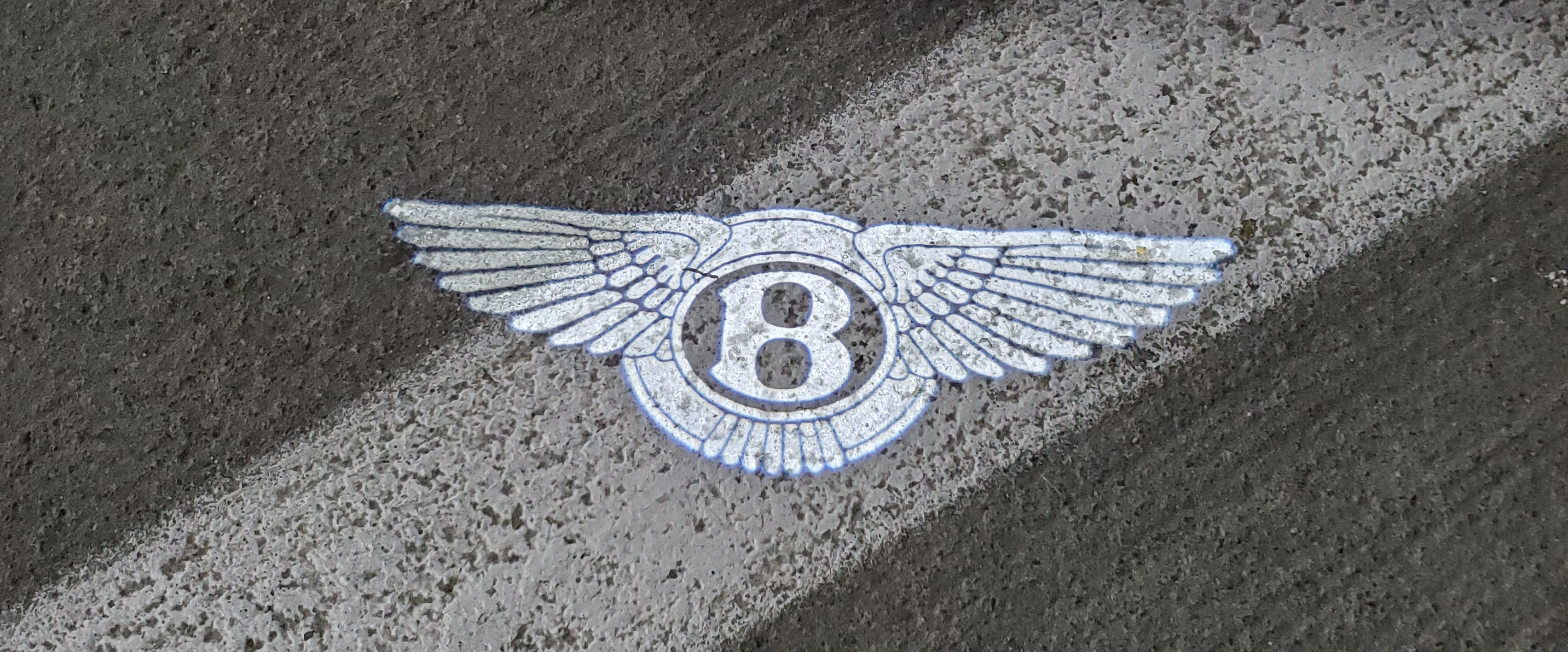 bentley logo projected from the puddle light of the continental gt v8