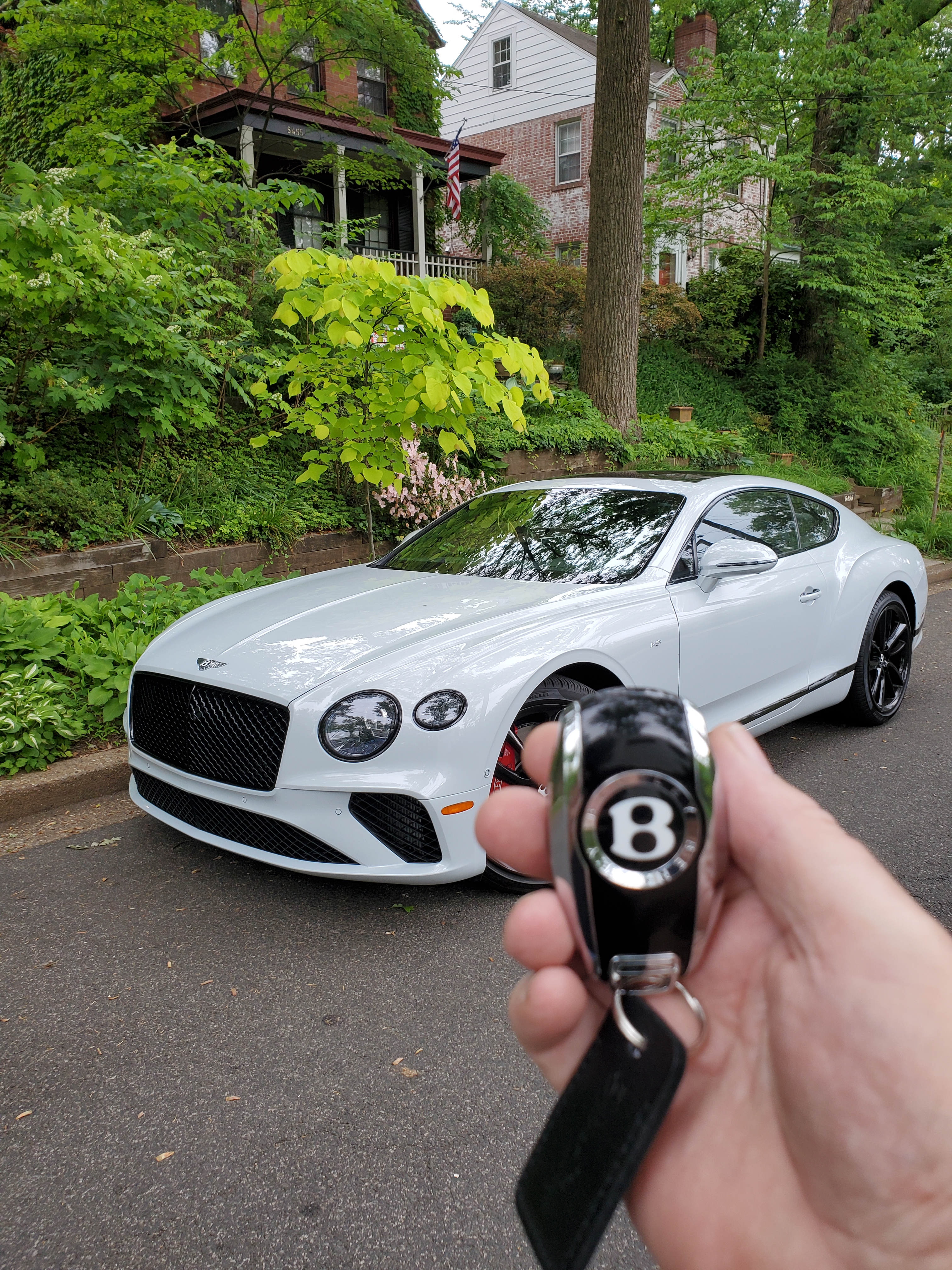 bentley continental gt v8 with key being held in front of it with a green space and house behind it