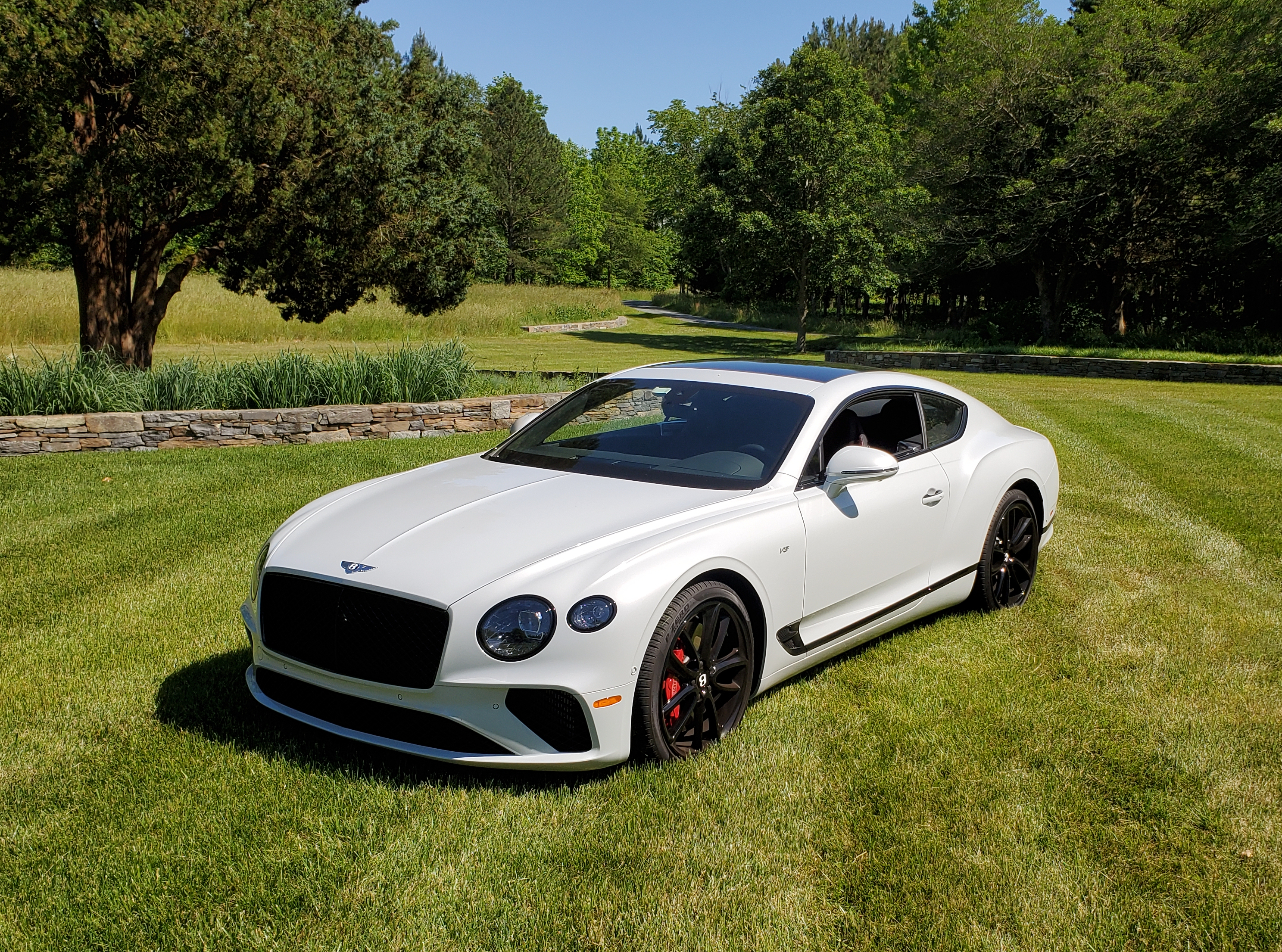 2021 Bentley Continental GT V8 in Ice on a grassy field with a stone wall and trees in the background