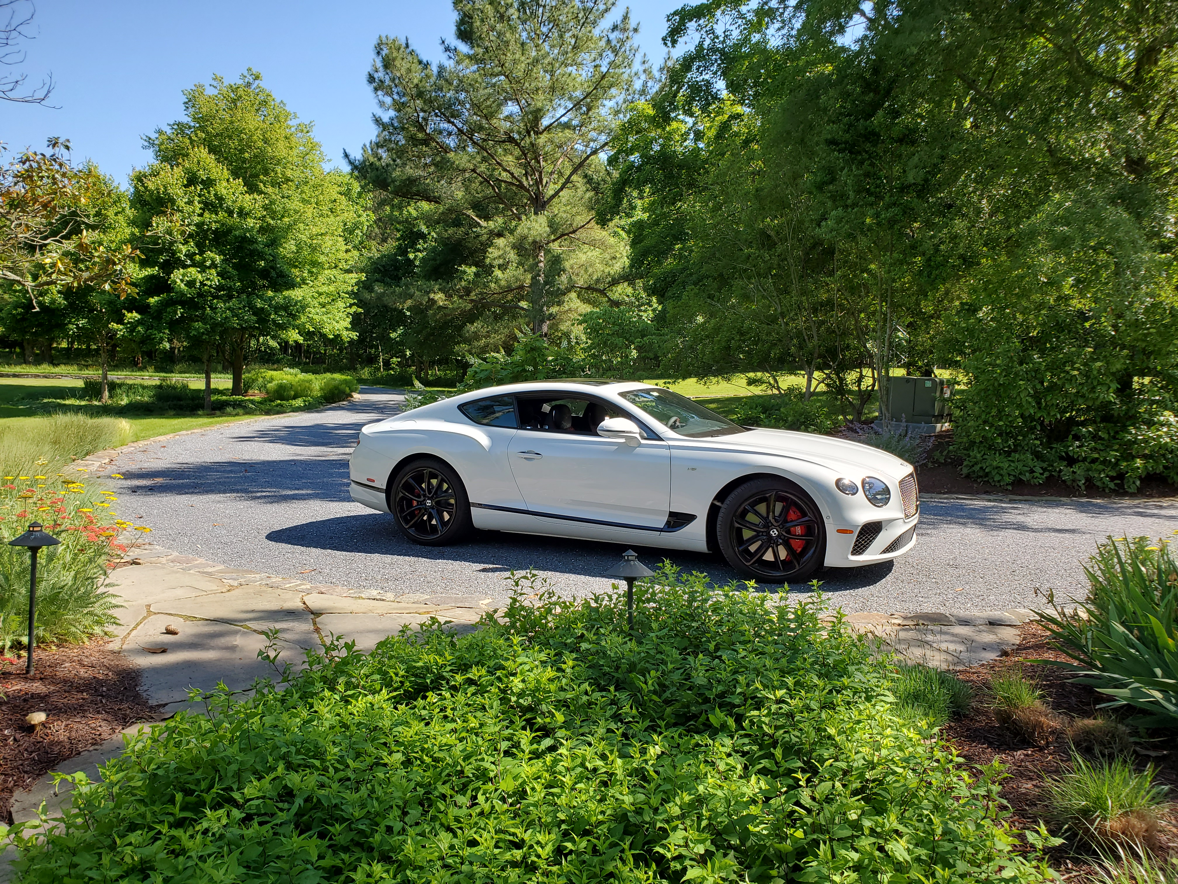 bentley continental gt v8 in ice on gravel driveway with greenery surrounding it