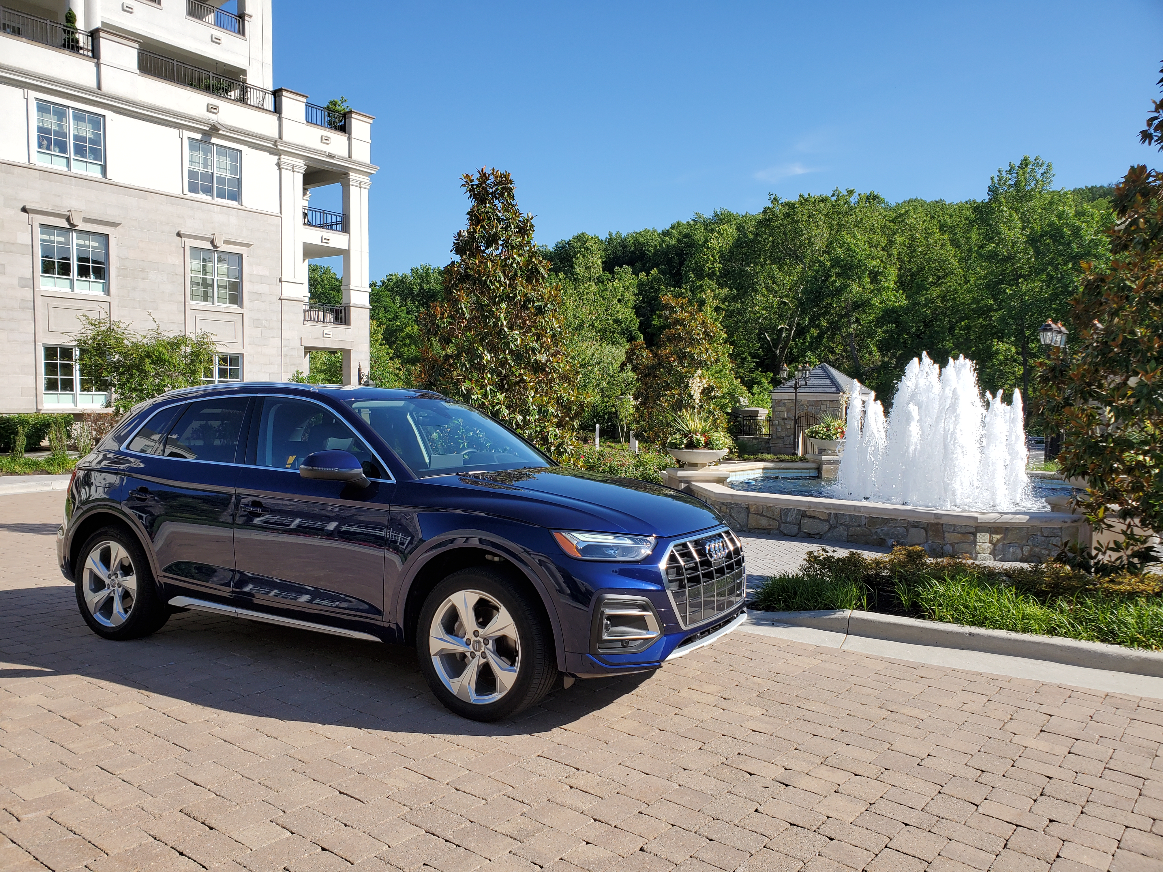 blue audi q5 in front of fountain of water